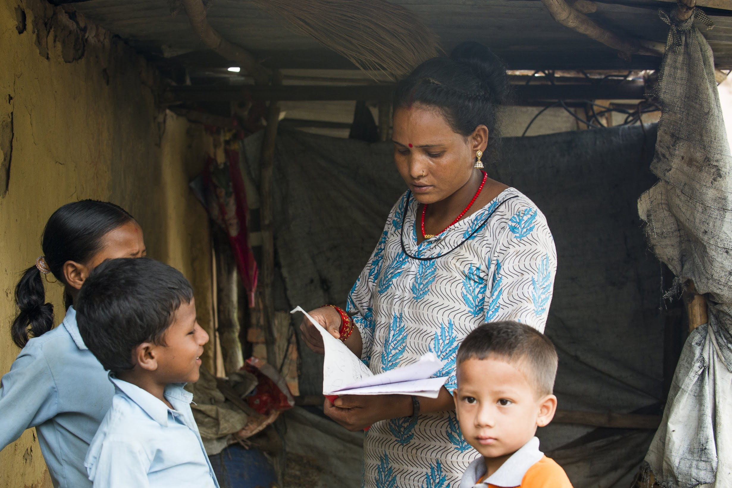 Dhana checks her children's homework before sending them off to school