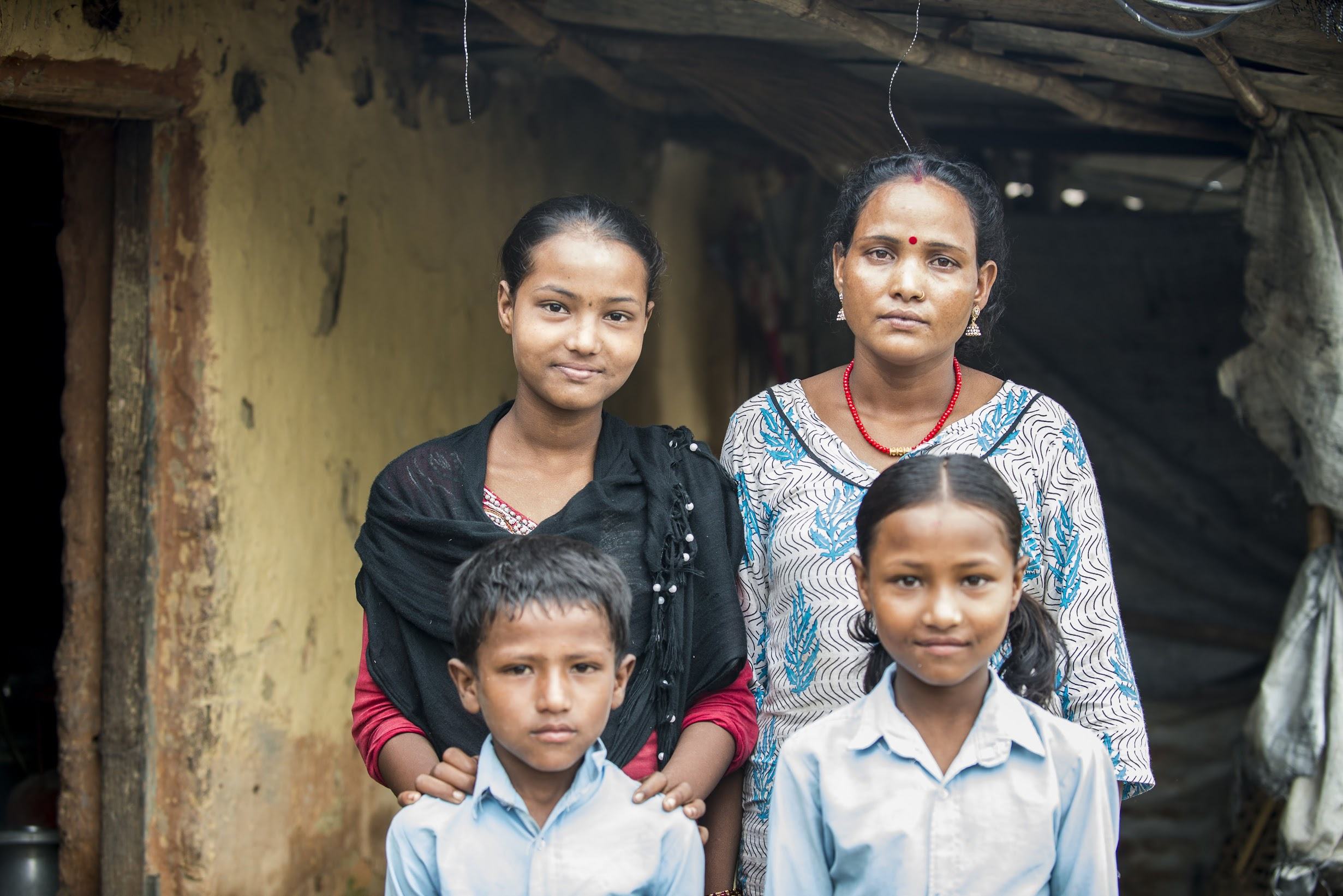 Dhana poses with her three children of her four children before they head to school and she heads to the Women's Center